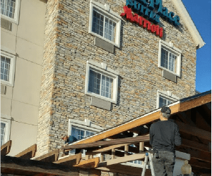 Best Buy Gutter team members installing a gutter system at the TownePlace Suites by Marriott